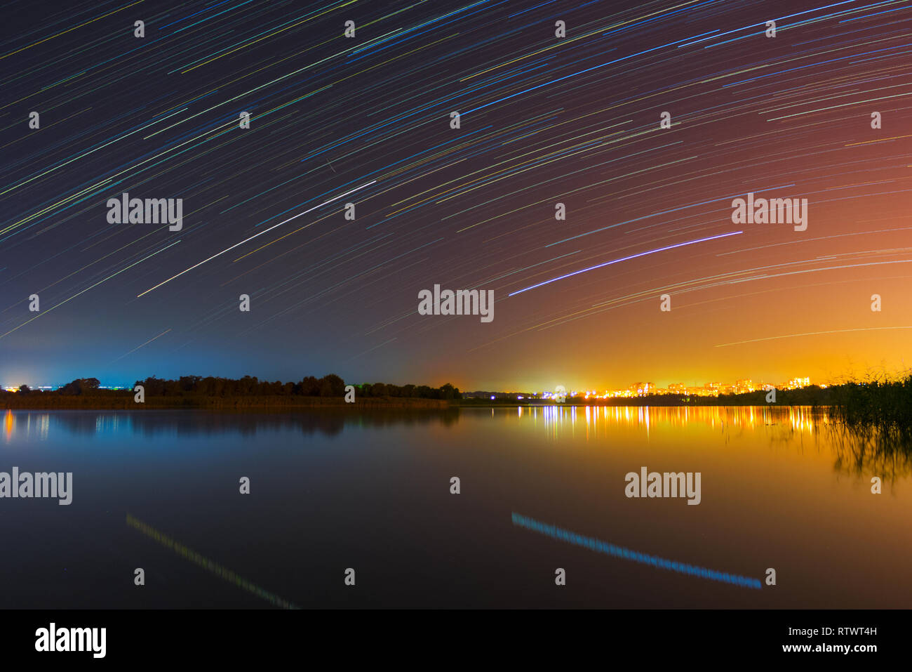 A star trails above the river. Long exposure photography. A city far away. - Stock Image