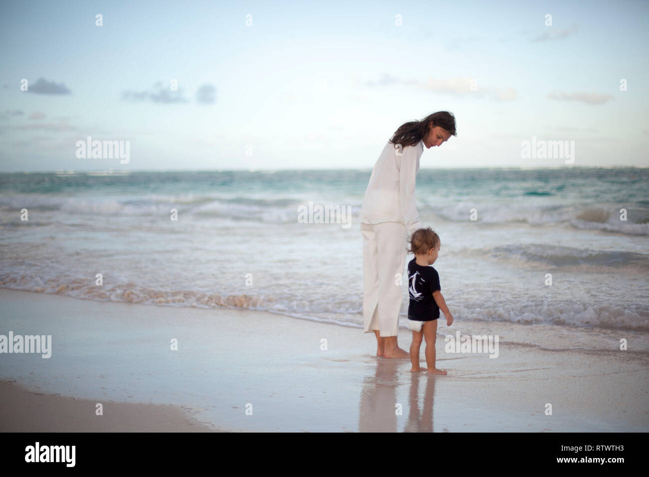 On sunset sand beach mother and little baby explores the ocean - Stock Image