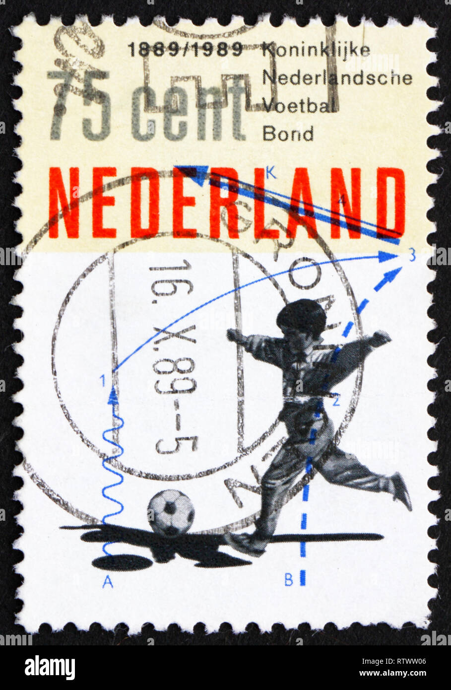 NETHERLANDS - CIRCA 1989: a stamp printed in the Netherlands shows Boy playing football, Centenary of Royal Dutch Soccer Association, circa 1989 Stock Photo