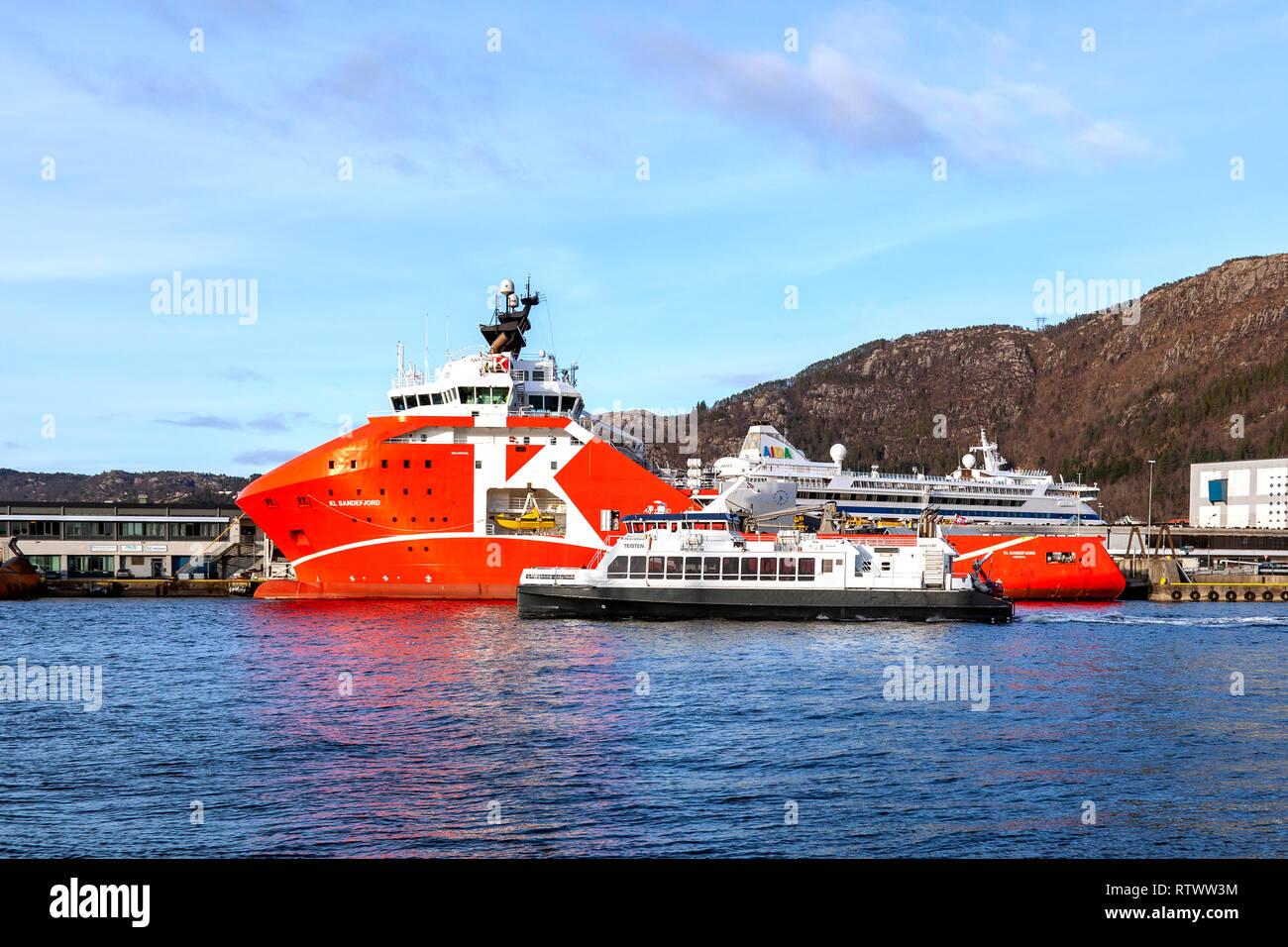 High speed passenger catamaran Teisten departing from the port of Bergen, Norway. Passing offshore supply vessel KL Sandefjord on it's way - Stock Image
