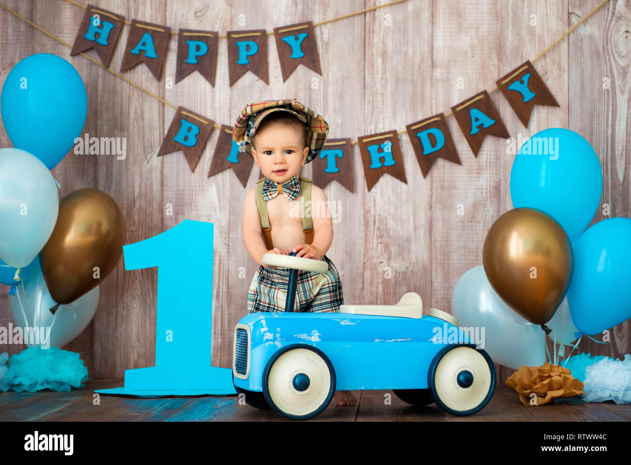 Little Boy Kid Gentleman In Retro Costume With Suspenders And Cap Is Sitting On A Wooden Car Childrens Party Balloons Happy Birthday 1 Year