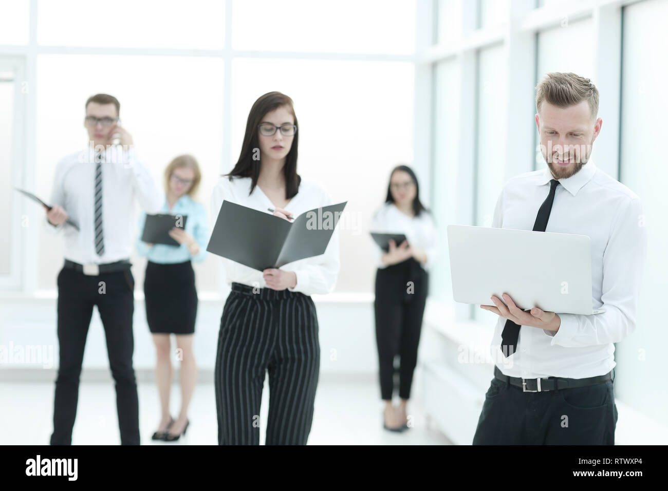 business team standing in the office hall before the business presentation. - Stock Image