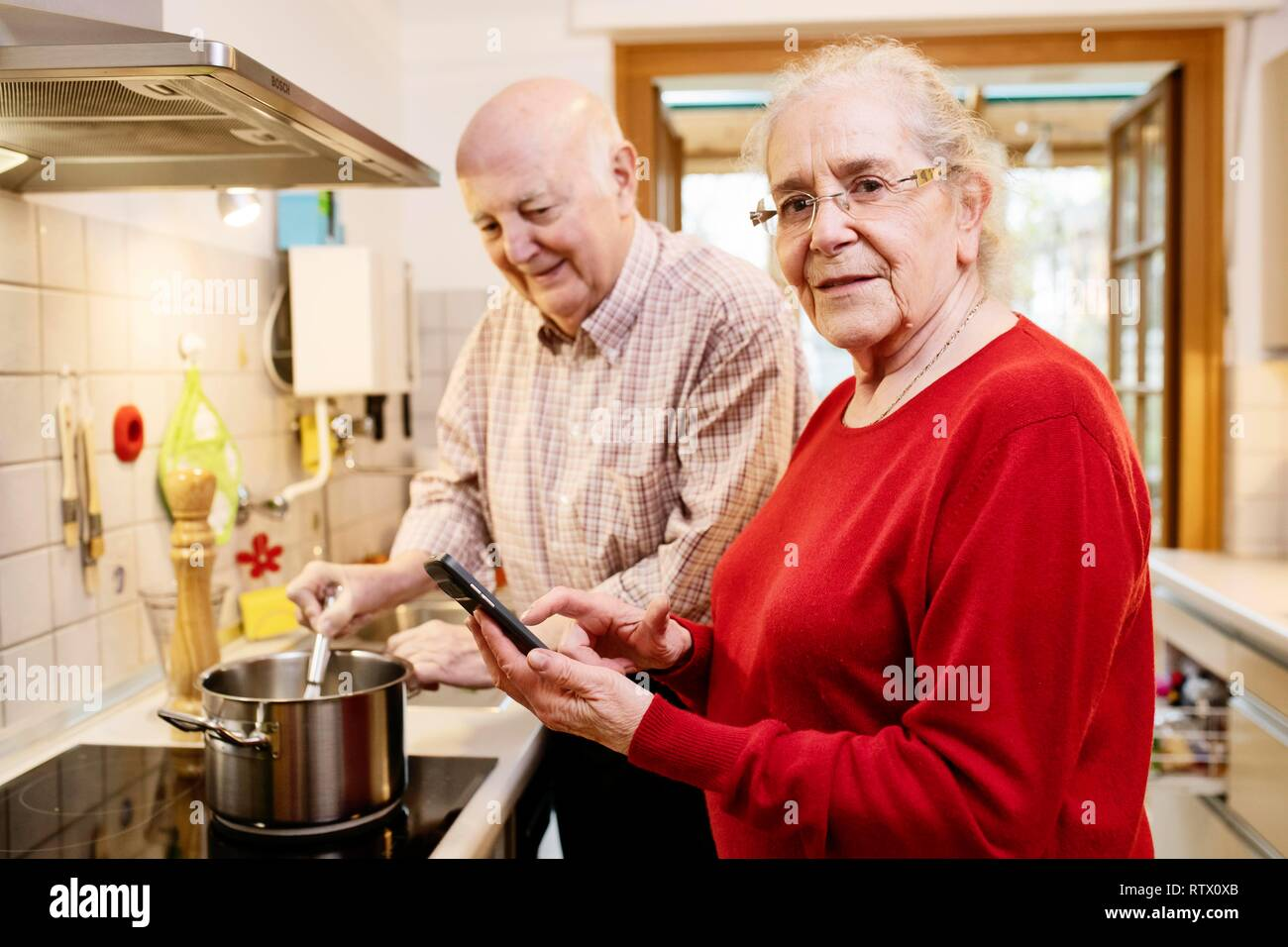 Senior couple standing at the stove cooking according to a recipe from the Internet, Germany - Stock Image