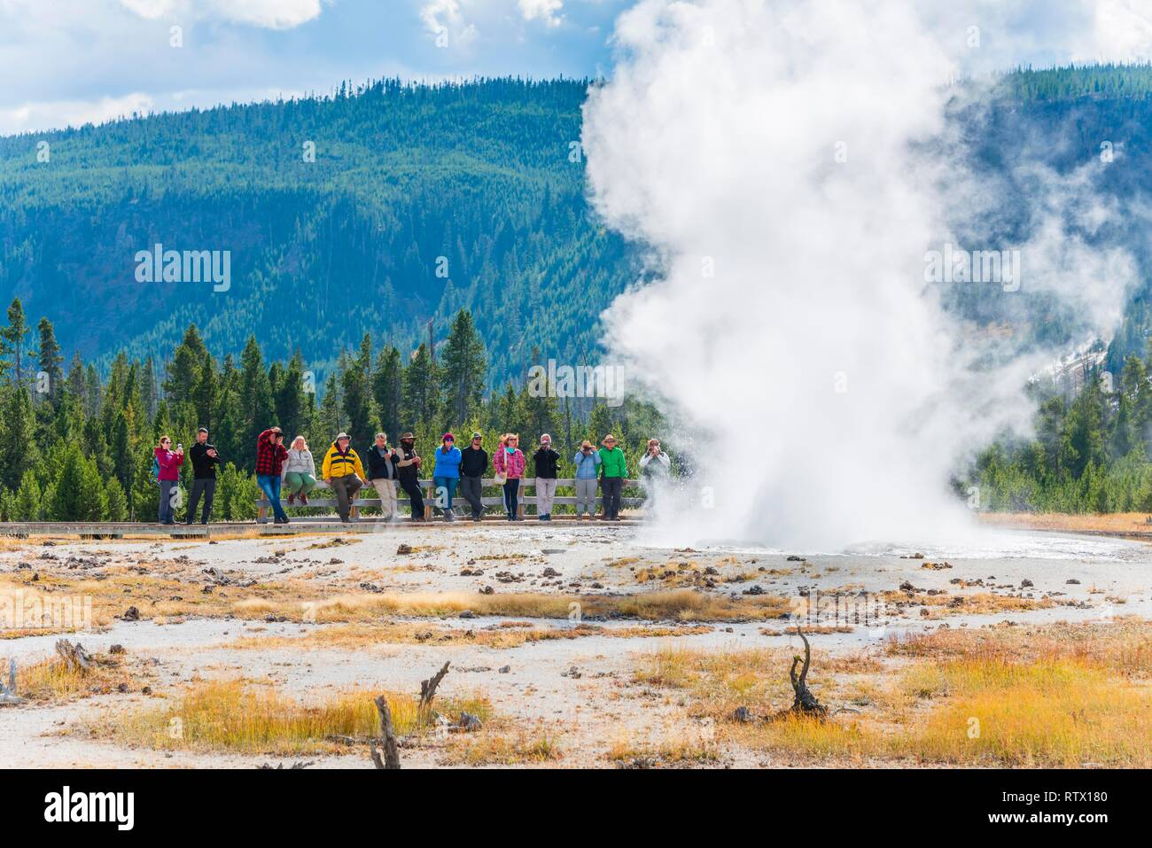 Tourists observe the eruption of the Geyser, Jewel Geyser, Black Sand Basin and Biscuit Basin, Yellowstone National Park - Stock Image