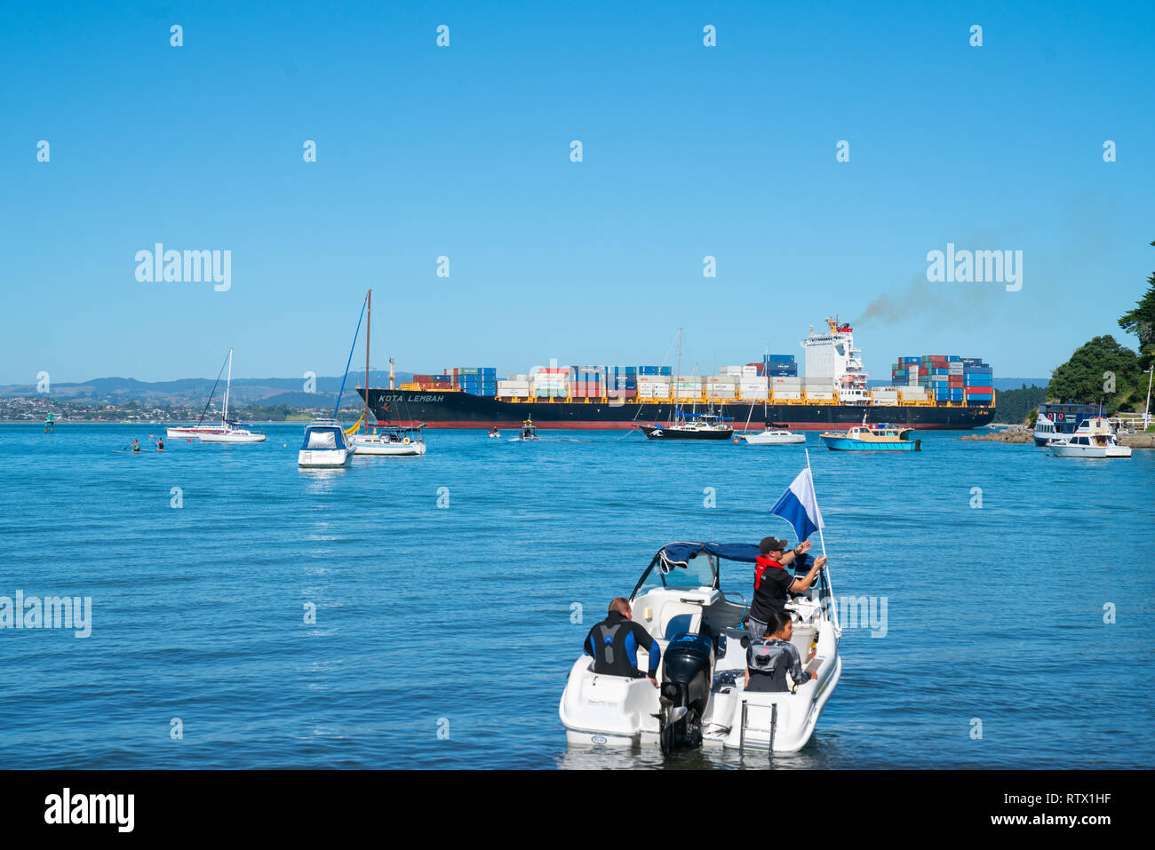 TAURANGA NEW ZEALAND - MARCH 3 2019; Boat and diver get ready to leave in the annual Pilot Bay environment clean-up as container cargo ship arrives th - Stock Image