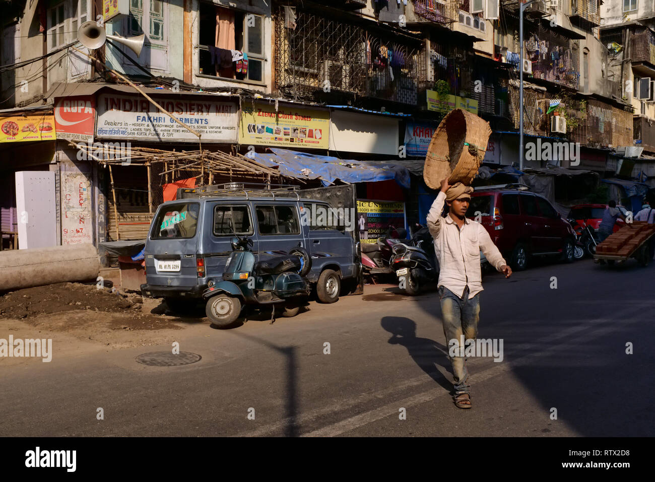 A porter with his empty basket raised over his head for more comfortable carrying, in Muslim-dominated Pydhonie area, Mumbai, India - Stock Image