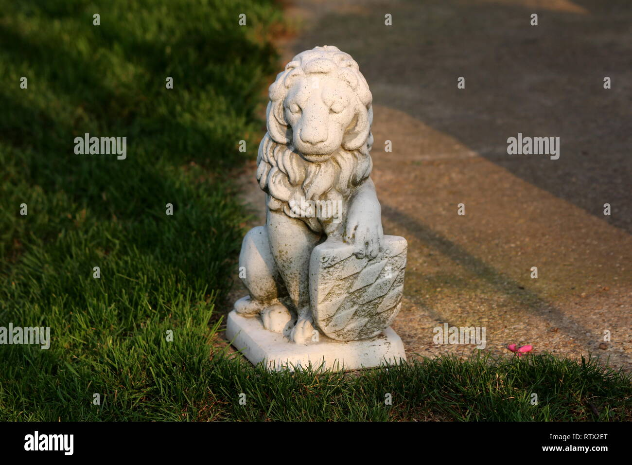 Concrete sculpture of mighty lion holding shield on edge of concrete path surrounded with grass on warm sunny day at sunset - Stock Image