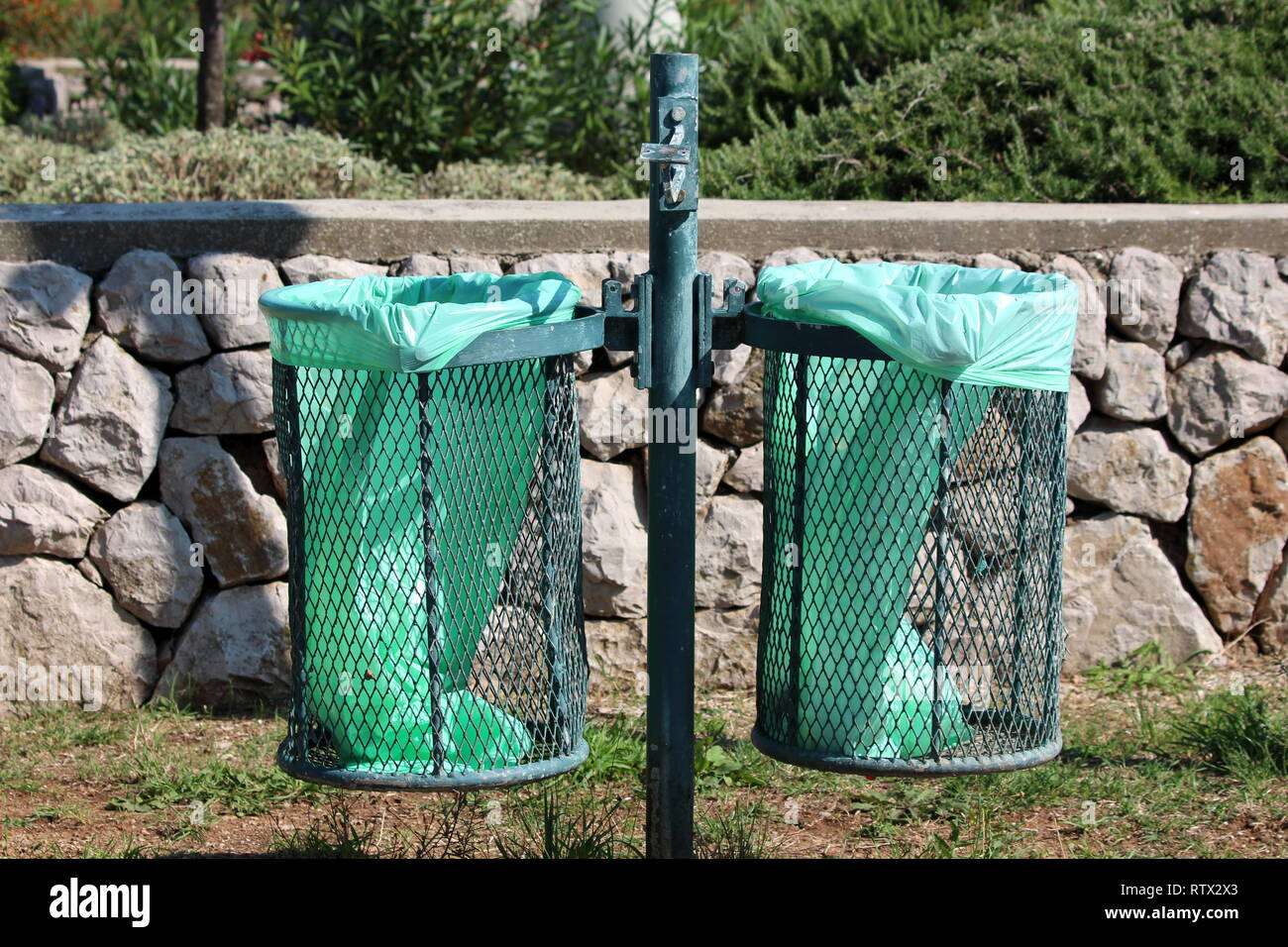 Green metal pole with dual outdoor public trash cans with fresh new nylon bags inserted and broken ashtray on top with traditional stone wall - Stock Image
