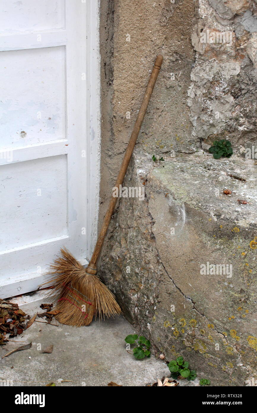 Heavily used house broom left in backyard after usage leaned on cracked dilapidated stone wall and wooden doors with fallen leaves on concrete tile Stock Photo