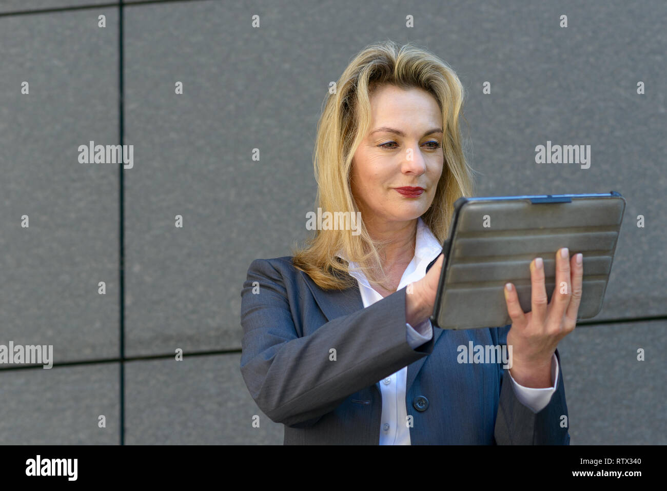 Mature businesswoman using a handheld tablet to surf the internet as she pauses in front of a grey stone wall in town - Stock Image