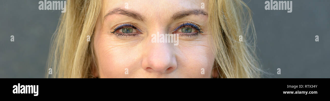 Close up cropped portrait of an attractive blond woman with blue eyes wearing makeup - Stock Image