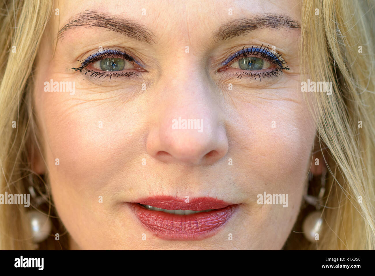 Close up cropped portrait of an attractive blond woman with blue eyes wearing makeup staring into the camera with parted lips - Stock Image