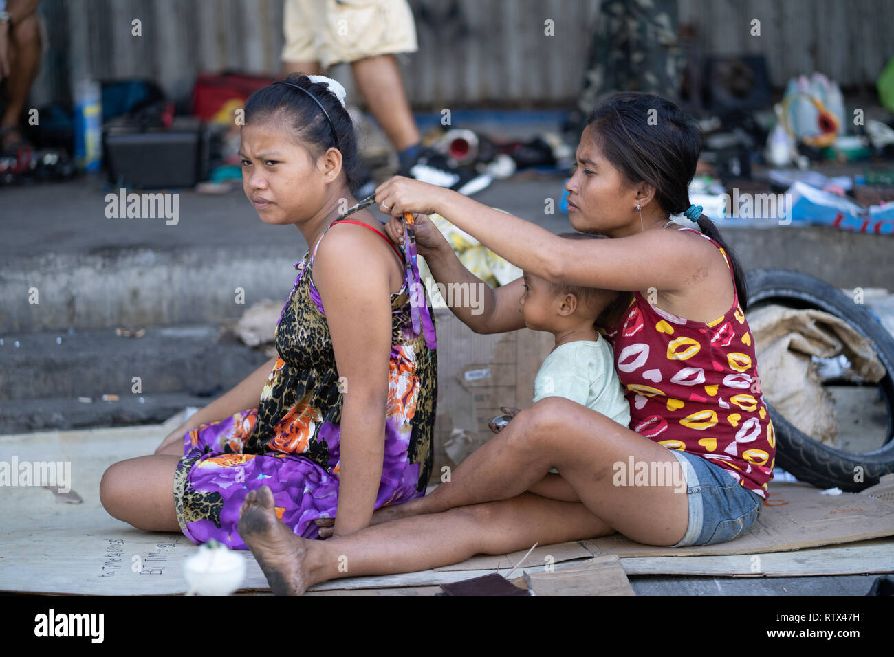 Two Filipino women,one without shoes,and a child sit on cardboard in a side street,Cebu City,Philippines - Stock Image