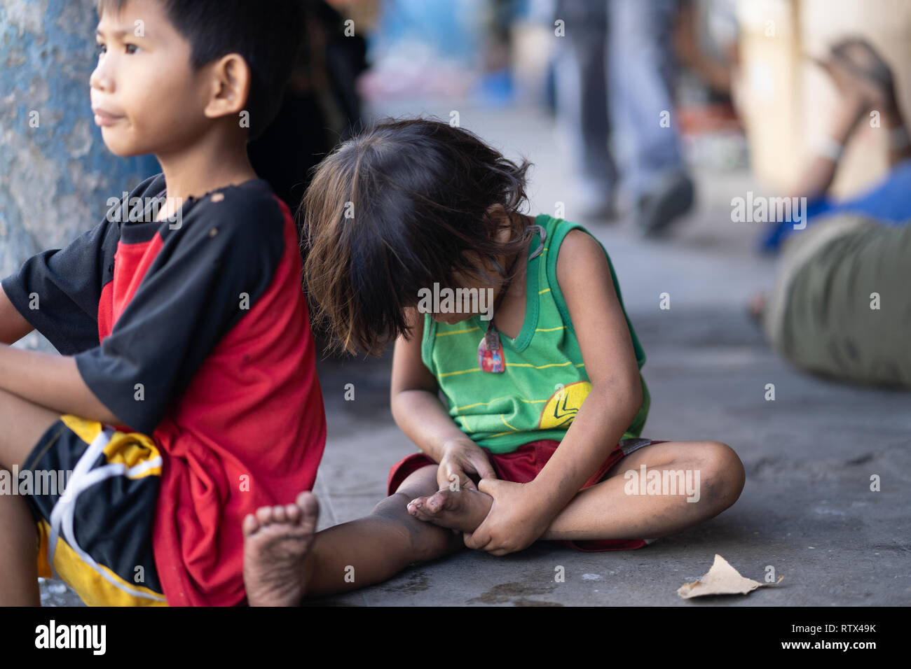 A child with no shoes sitting on a sidewalk within Cebu City,Philippines - Stock Image