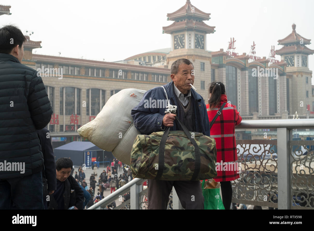 Chinese elderly migrant worker goes out of the Beijing railway station. China's ageing society problem appears to be worsening. 03-Mar-2019 - Stock Image