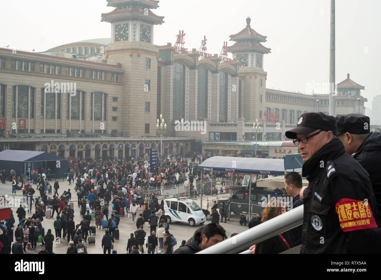 Two security men watch the crowd in Beijing railway station. China bans 23m from buying travel tickets as part of 'social credit' system 03-Mar-2019 - Stock Image