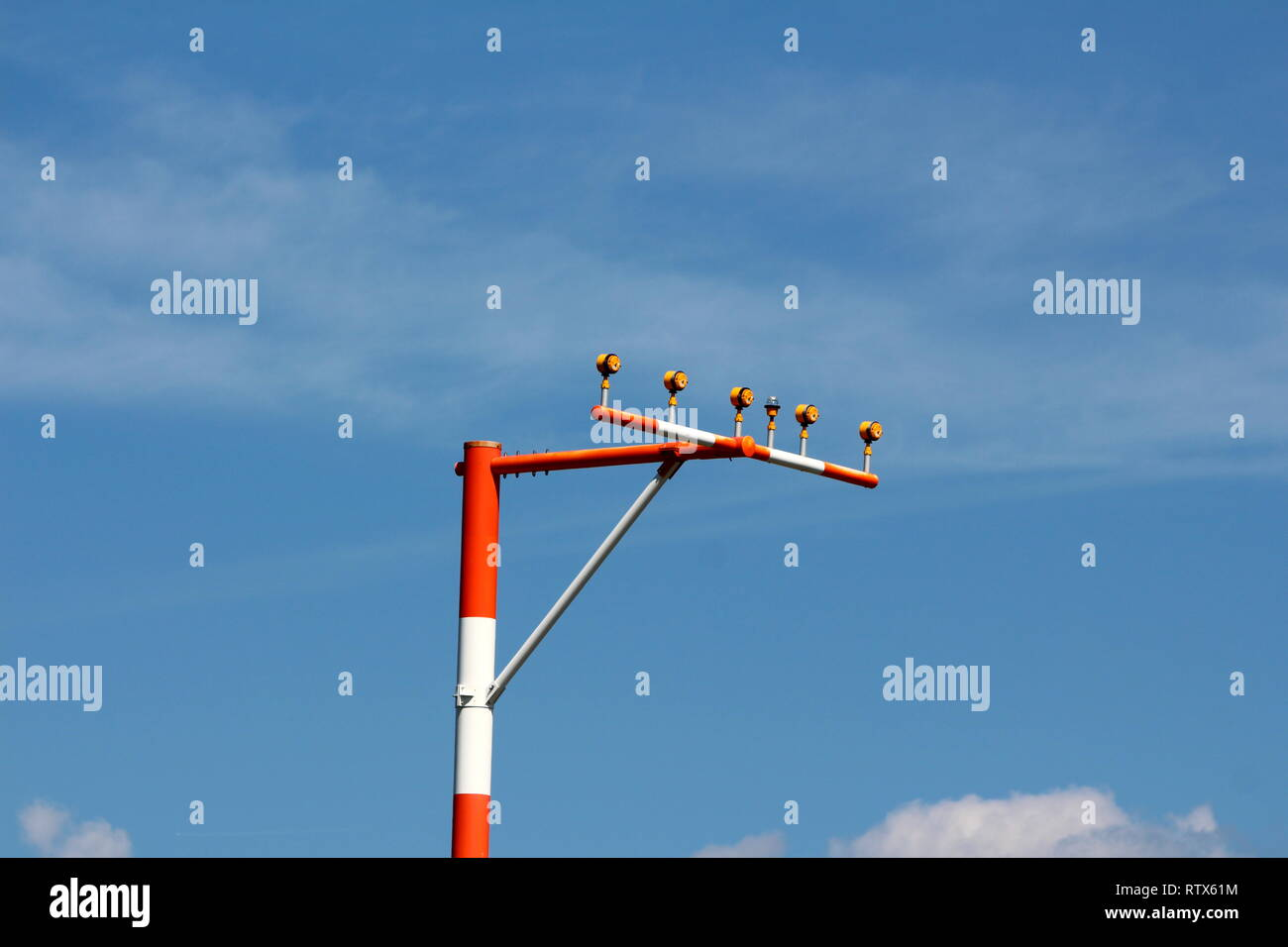 Single high metal red and white pole with multiple airport runway guiding lights on cloudy blue sky background - Stock Image