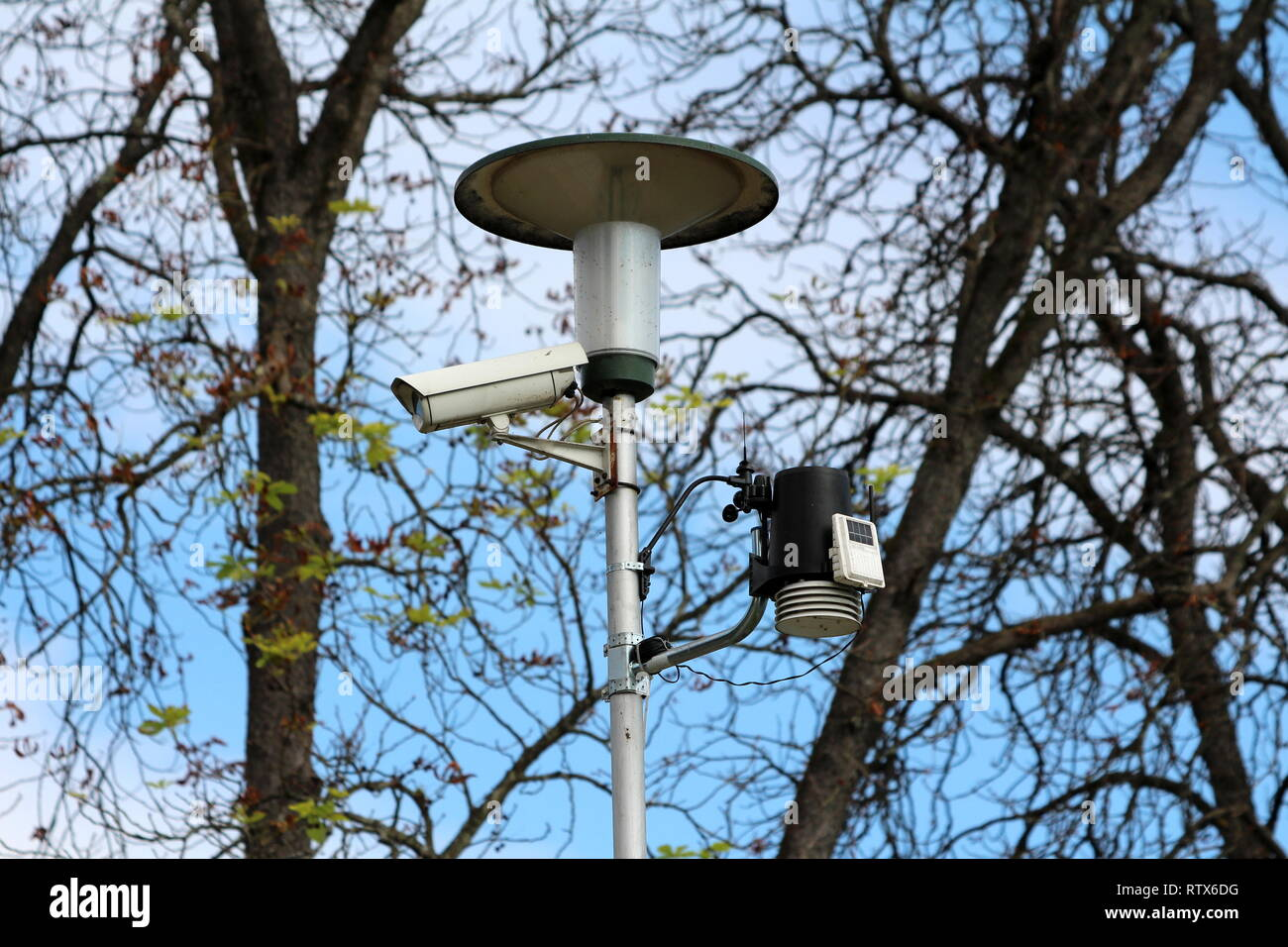 Street light on metal post with mounted surveillance camera and various measuring devices with clear blue sky and trees in background Stock Photo