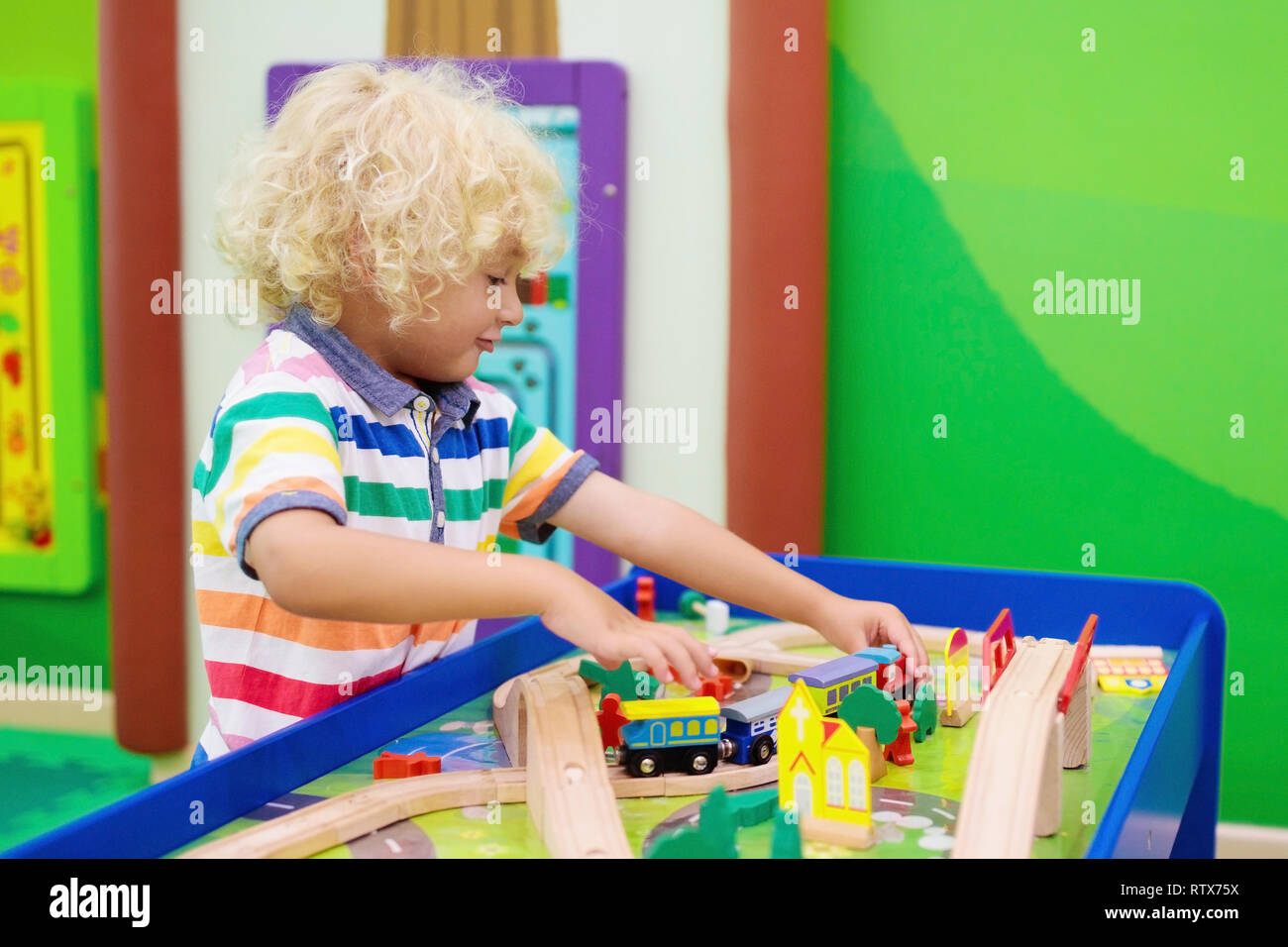 Kids Play Toy Railroad Little Blond Curly Boy With Wooden Trains In