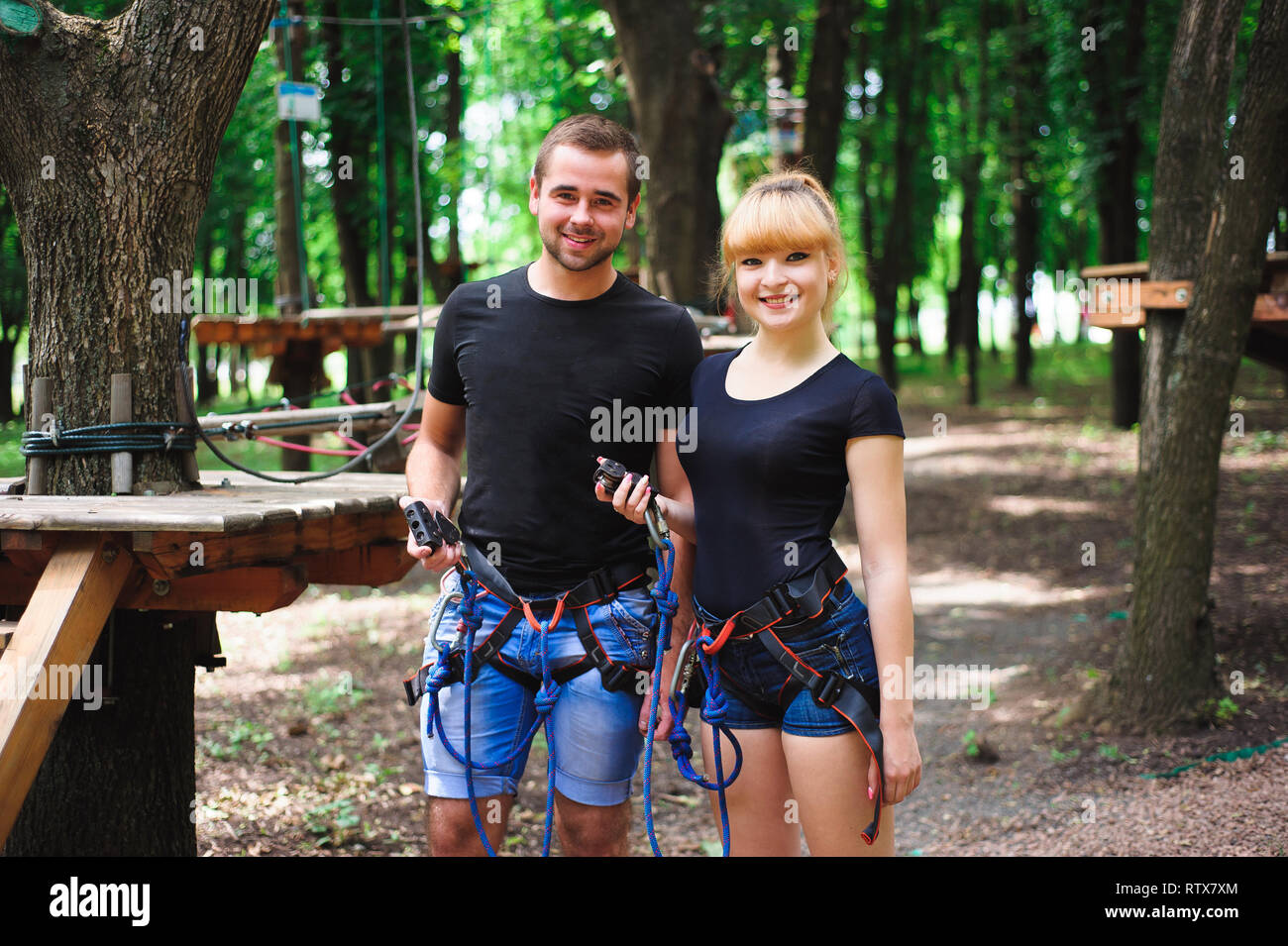 adventure climbing high wire park - hiking in the rope park two young people in safety equipment. - Stock Image