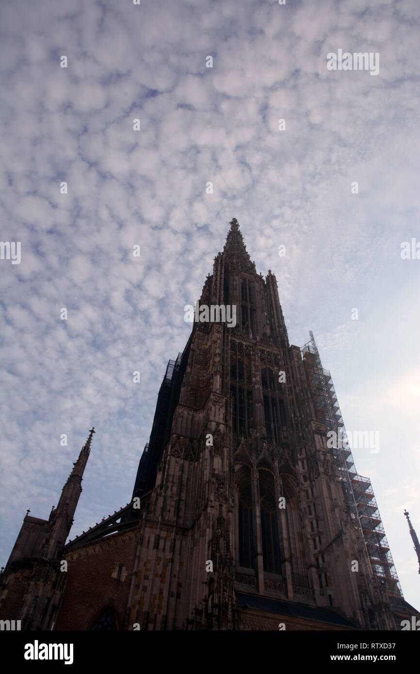 tallest steeple of a church exterior view the minster of ulm overexposed abstract look, Ulm Minster exterior view from the west in front of blue sky c Stock Photo