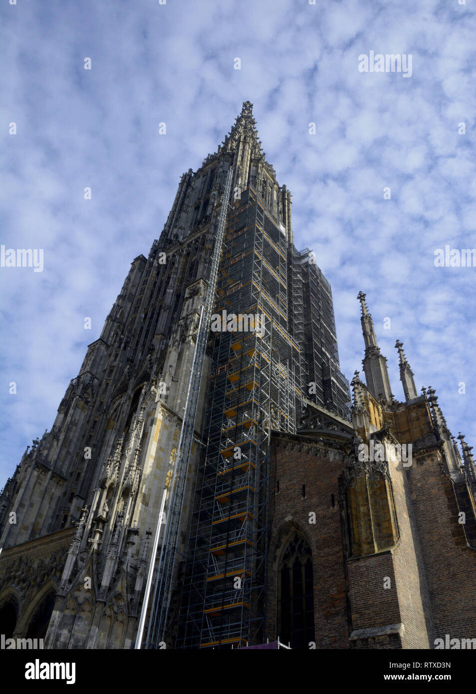 Ulm Minster exterior view from the west in front of blue sky covered with small clouds, tallest church of the world the minster of ulm abstract exteri Stock Photo