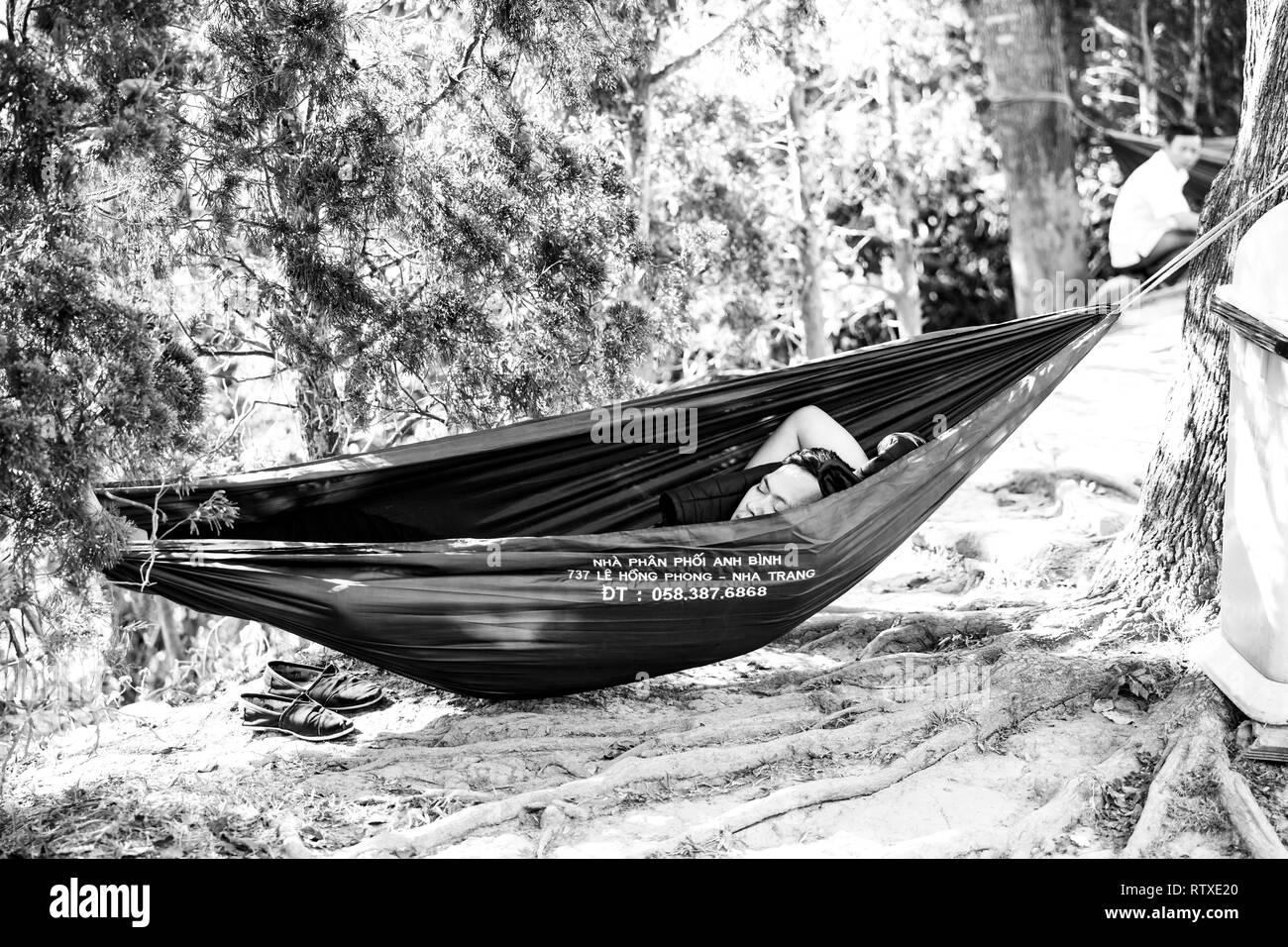 DA LAT, VIETNAM - FEBRUARY 20, 2018: Bus driver sleeps in a hammock during his lunch break in Da Lat, Vietnam - Stock Image