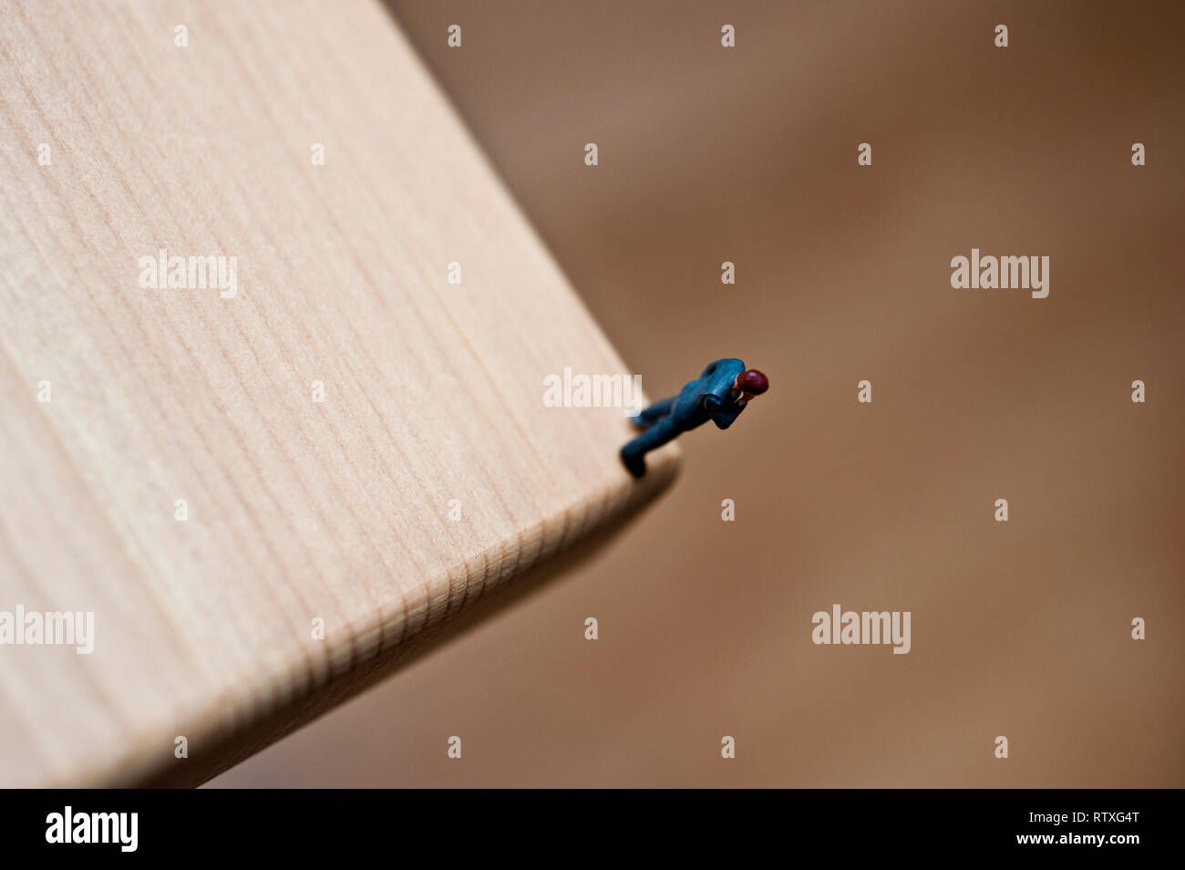 miniature figurine on the corner of a table, concept for man on the edge - Stock Image