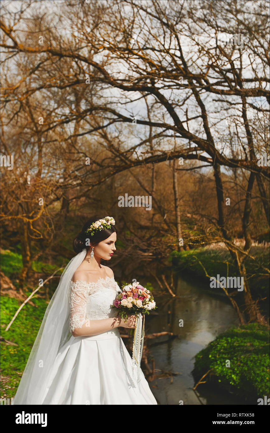 19b77cfbcc8 Elegant and fashionable young brunette bride with bright makeup and with a  floral wreath on her