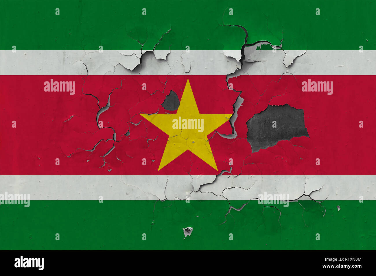Close up grungy, damaged and weathered Suriname flag on wall peeling off paint to see inside surface. - Stock Image