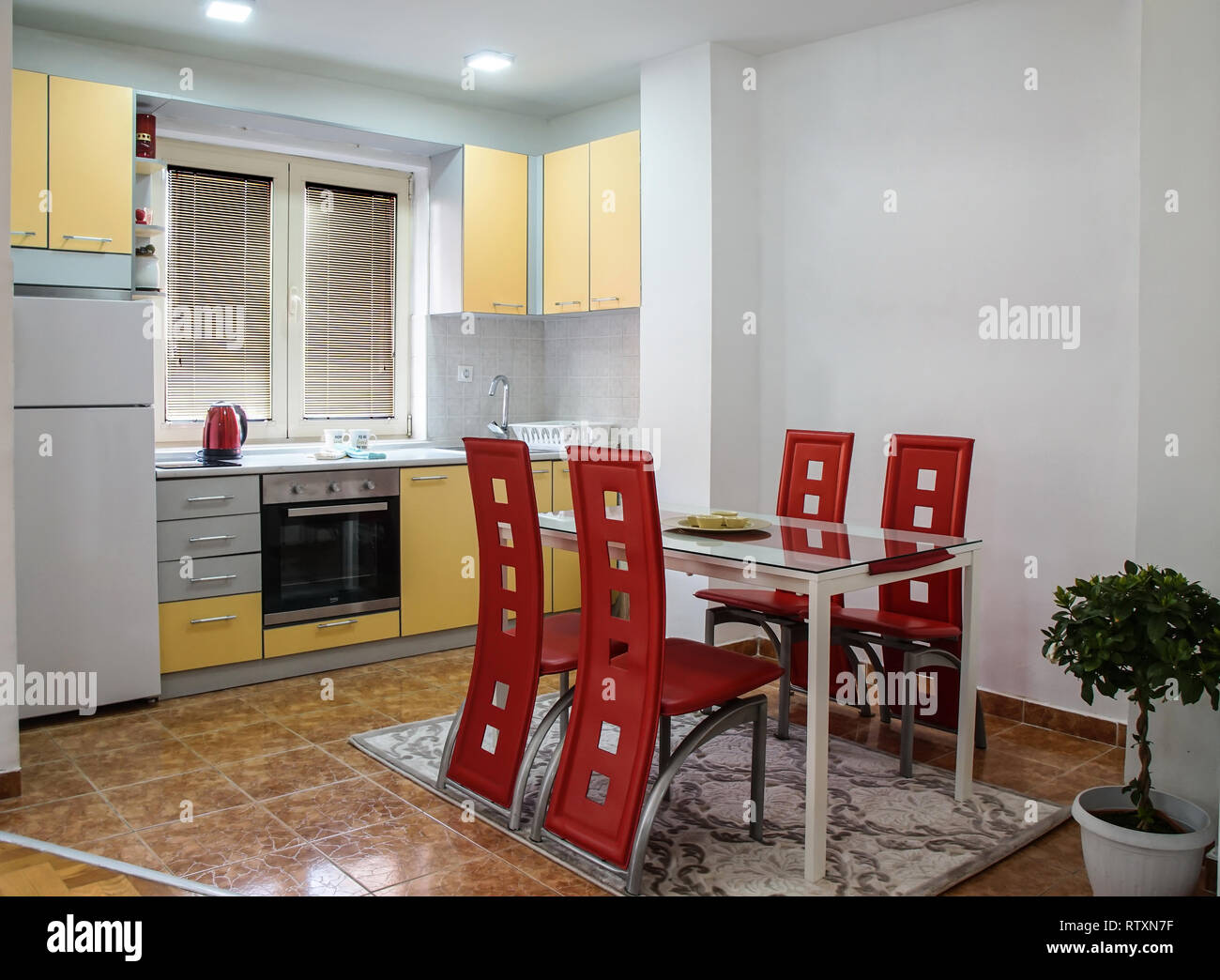 Modern kitchen with dining area with nice red leather chairs ...