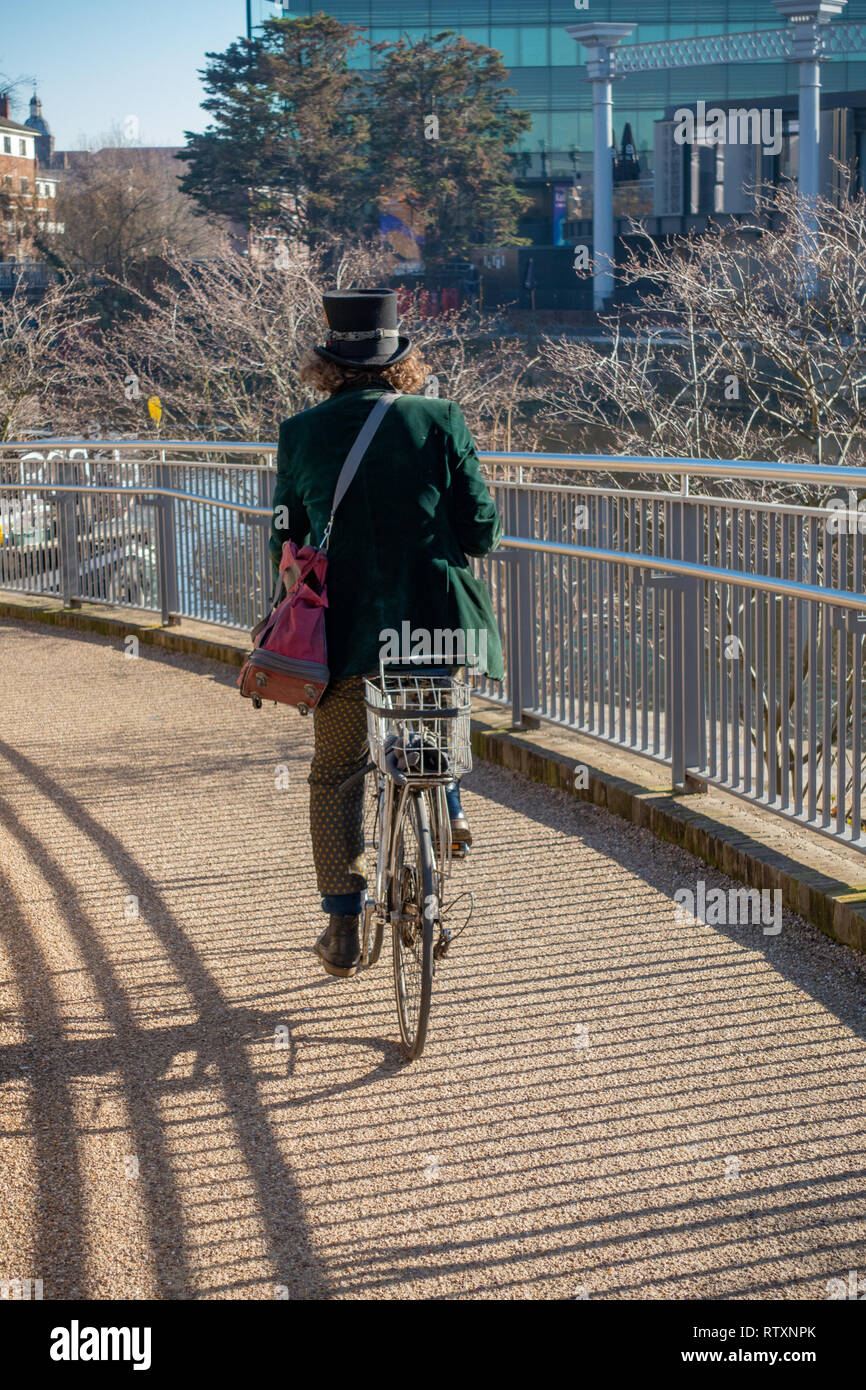Eccentrically dressed man wearing a Top Hat and wearing a Green Velvet Jacket riding a pushbike at Coal Drops Yard, Kings Cross, London, England. Stock Photo