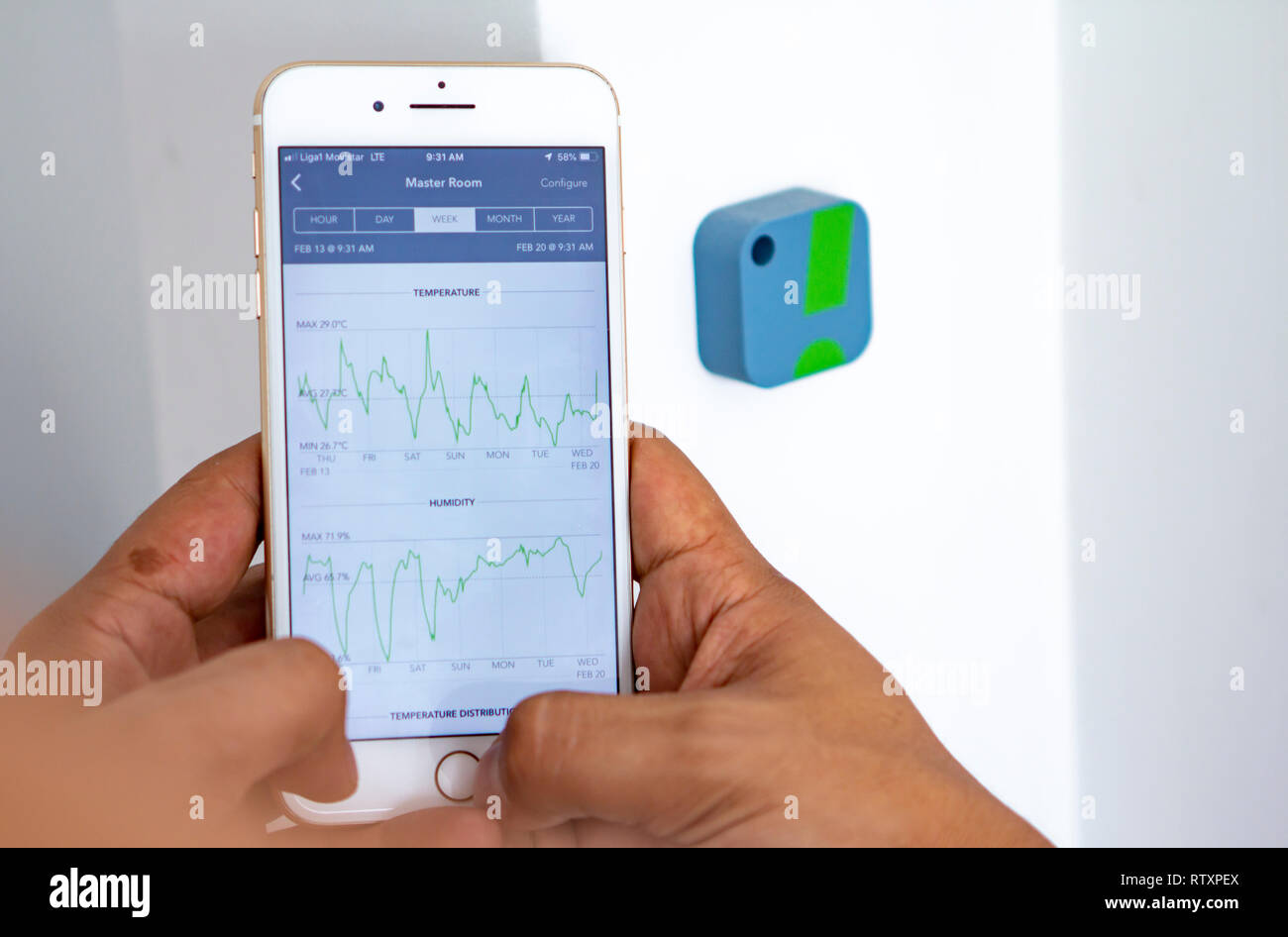 Man monitoring home humidity levels with app - Stock Image