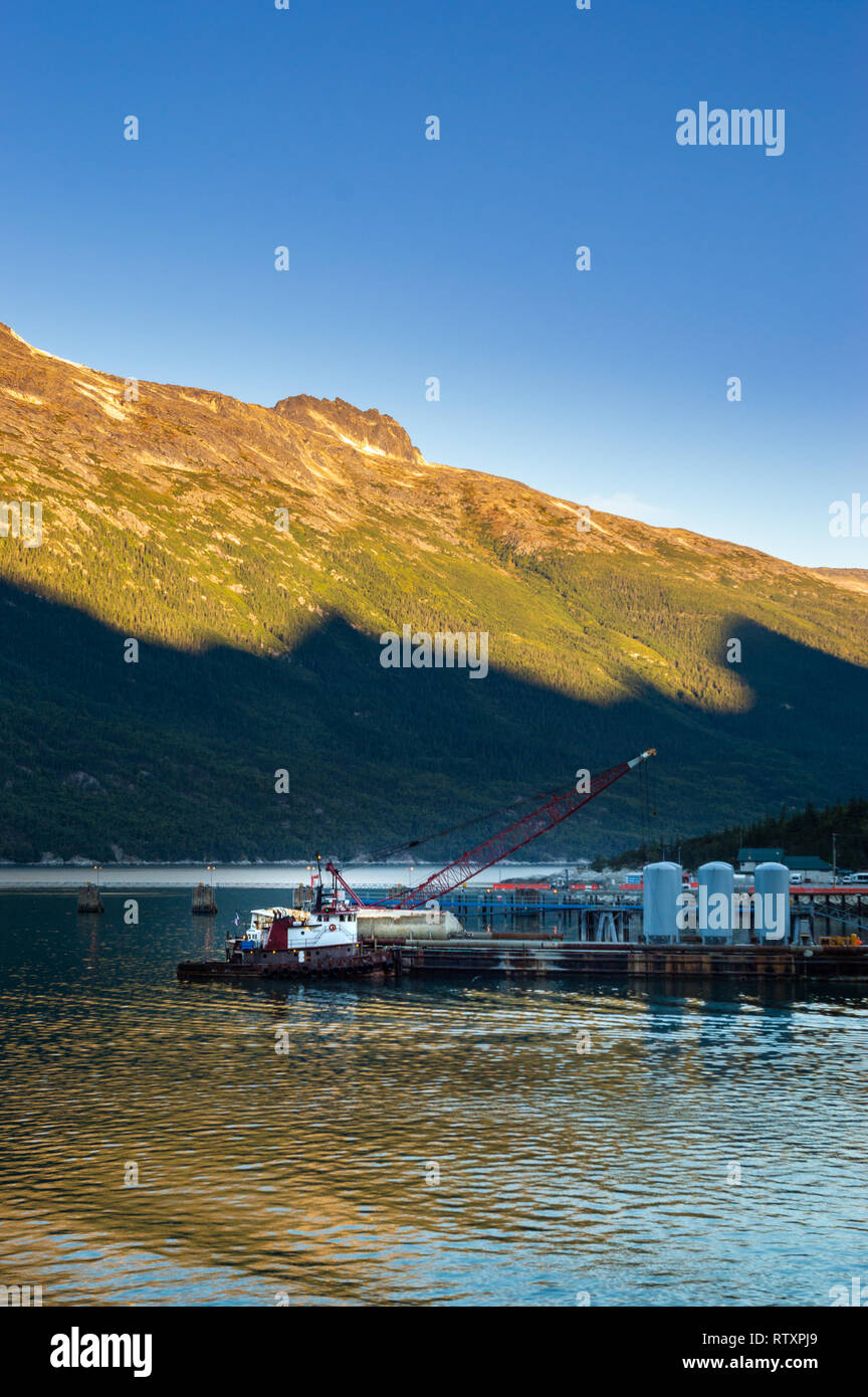 September 15, 2018 - Skagway, AK: Broadway Dock industrial cargo wharf with tugboat and crane at sunrise. - Stock Image