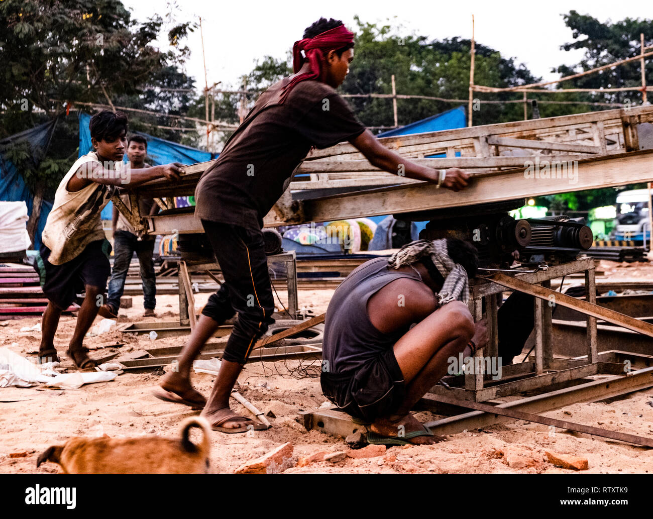 A group of young men dismantling a ferris wheel at the fair grounds Sahid Nagar, Bhubaneshwar. - Stock Image