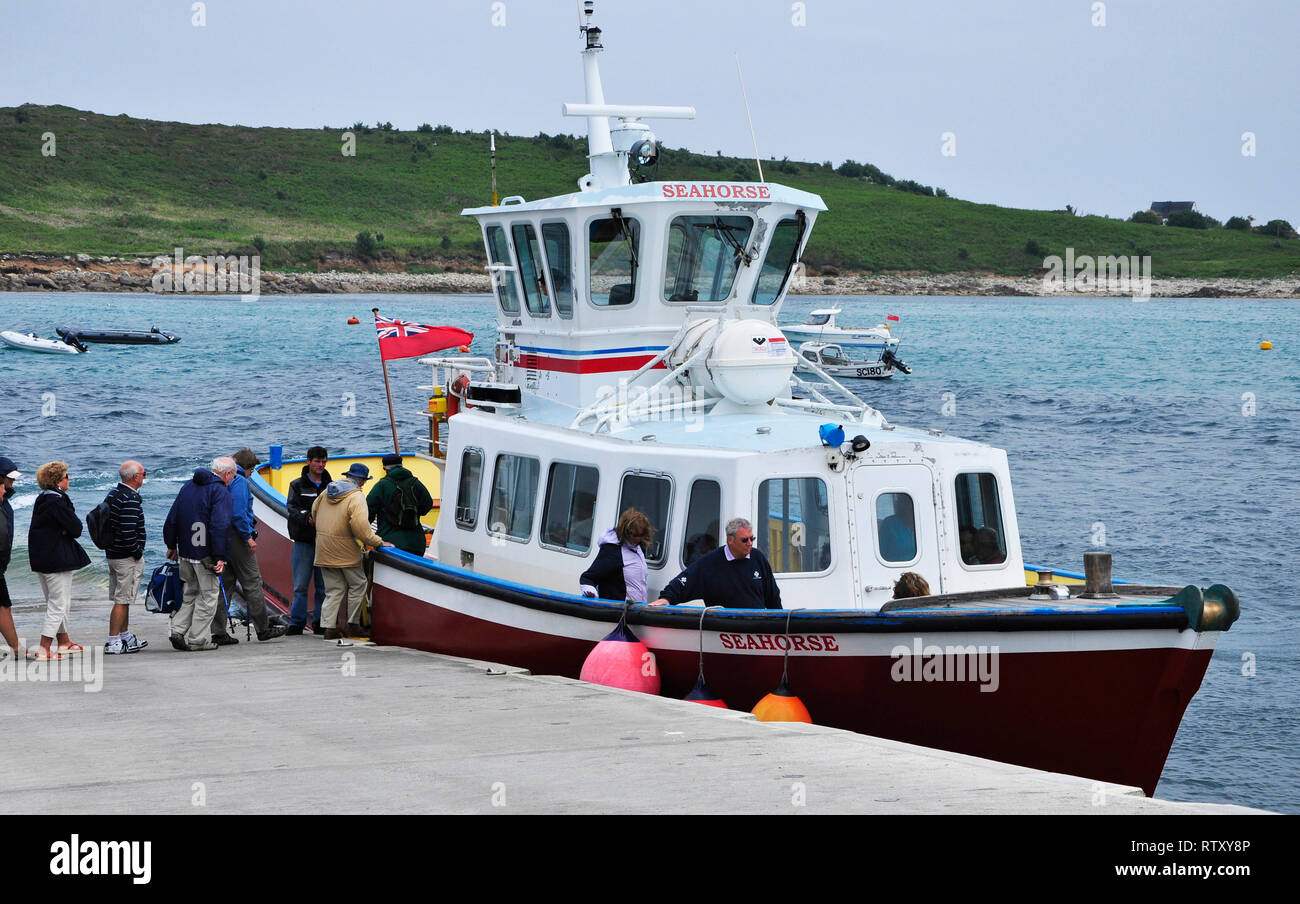 Visitors embark on Seahorse to return to St Marys from Agnes in the Isles of Scilly after a day walking around the island.Cornwall, England,UK - Stock Image