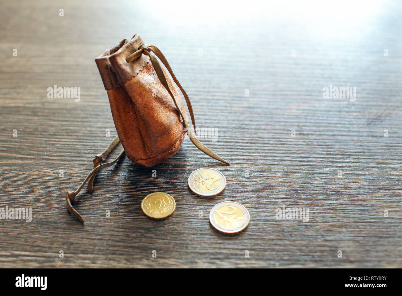 Vintage leather pouch on wooden desk, with euro coins next to it - Stock Image