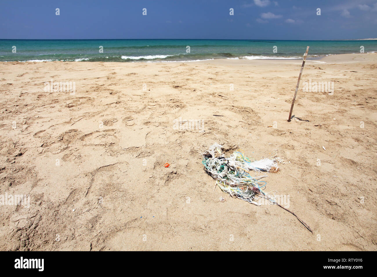 Beautiful empty beach, small pile of rubbish (tangled plastic ropes) on fine sand. Ocean littering concept. Karpass, Northern Cyprus - Stock Image