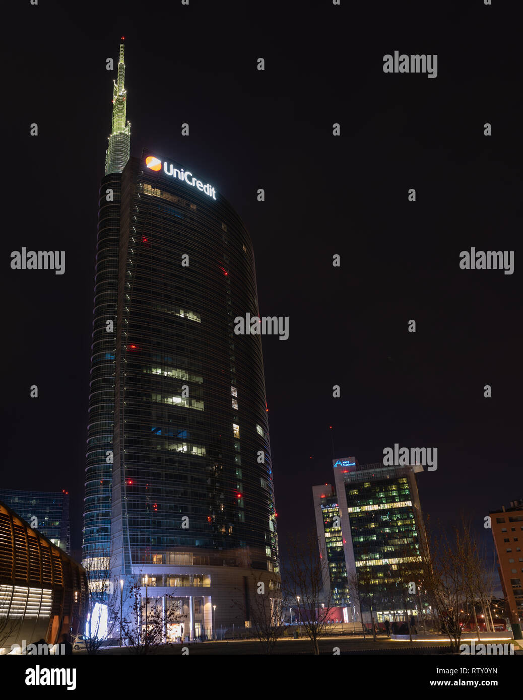 03/02/2019 Mialn, Italy: Unicredit tower, Gae Aulenti square, financial district of milan seen from the new park, the trees library. nocturnal scene Stock Photo