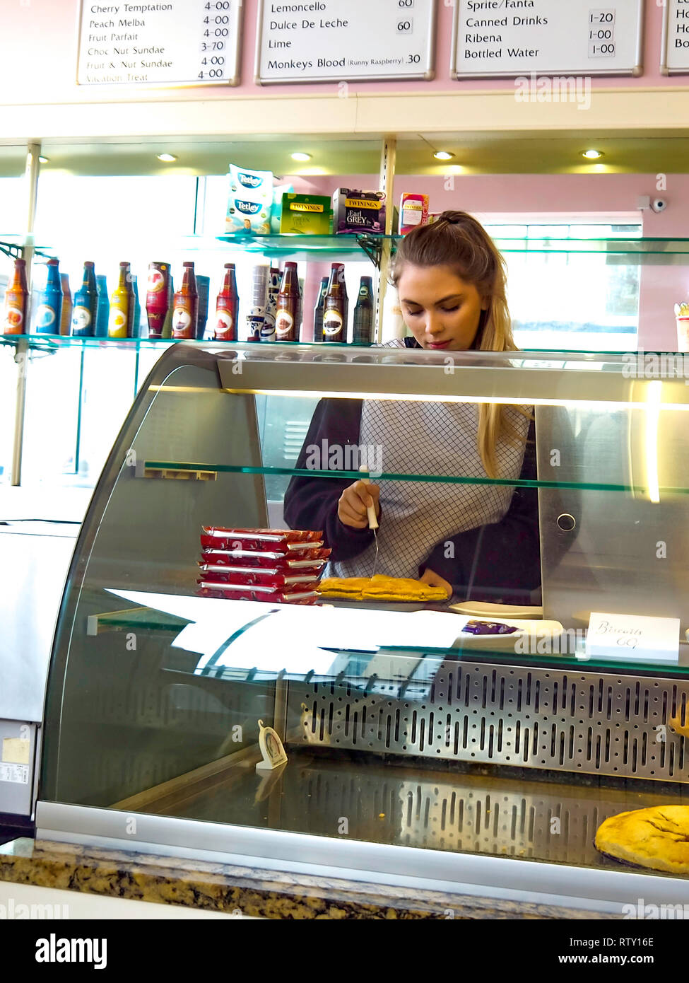 A young waitress in an ice cream parlour in North Yorkshire England carefully cutting a slice of home-made apple pie Stock Photo