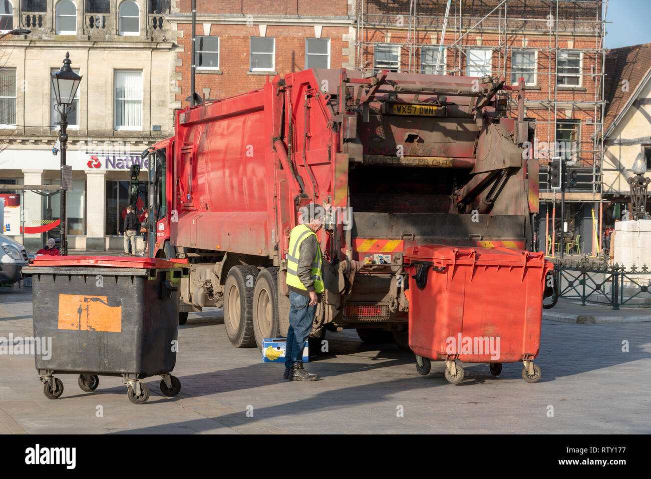 Salisbury, Wiltshire, England, UK. February 2019. Operative loading a commercial size red refuse bin into a truck in the city centre. - Stock Image