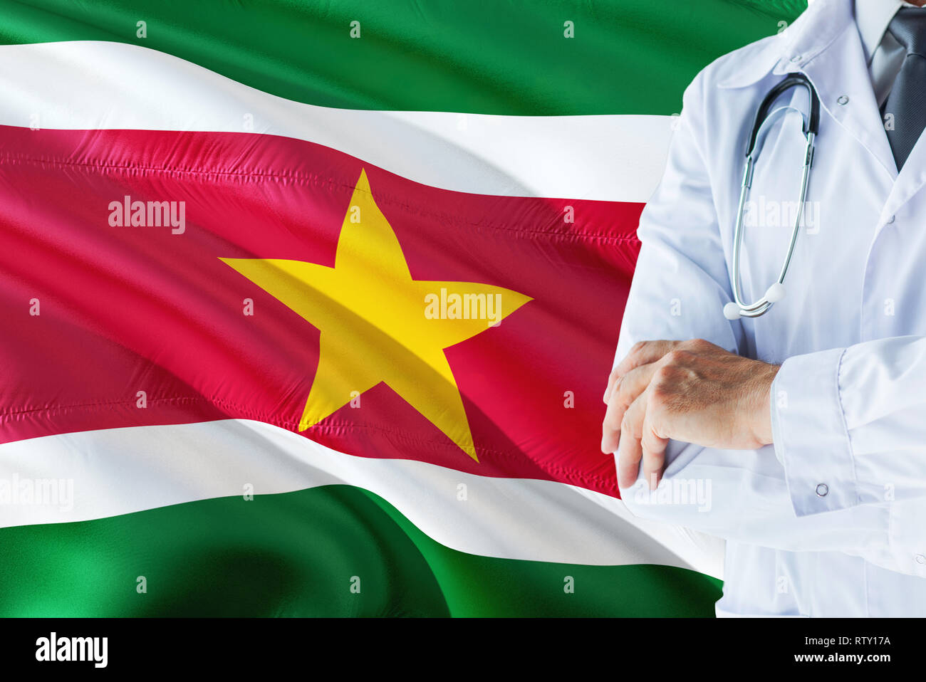 Surinamese Doctor standing with stethoscope on Suriname flag background. National healthcare system concept, medical theme. - Stock Image