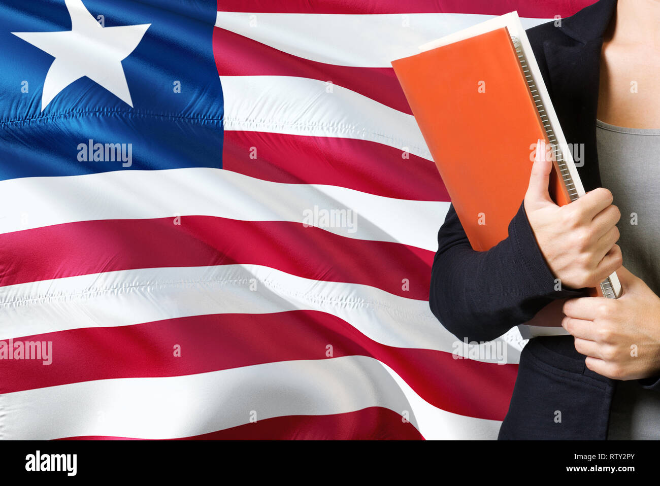 Learning Liberian language concept. Young woman standing with the Liberia flag in the background. Teacher holding books, orange blank book cover. - Stock Image