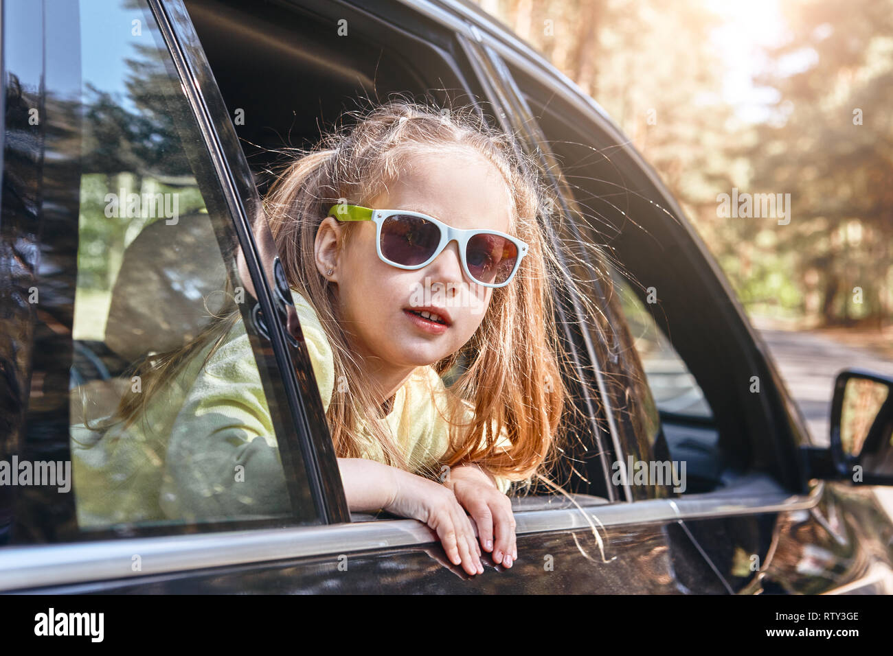 7e45df3bb76e Five years old blond caucasian child girl, wearing sunglasses and looking  out the window while traveling with her parents in a car. Safe trip, journey