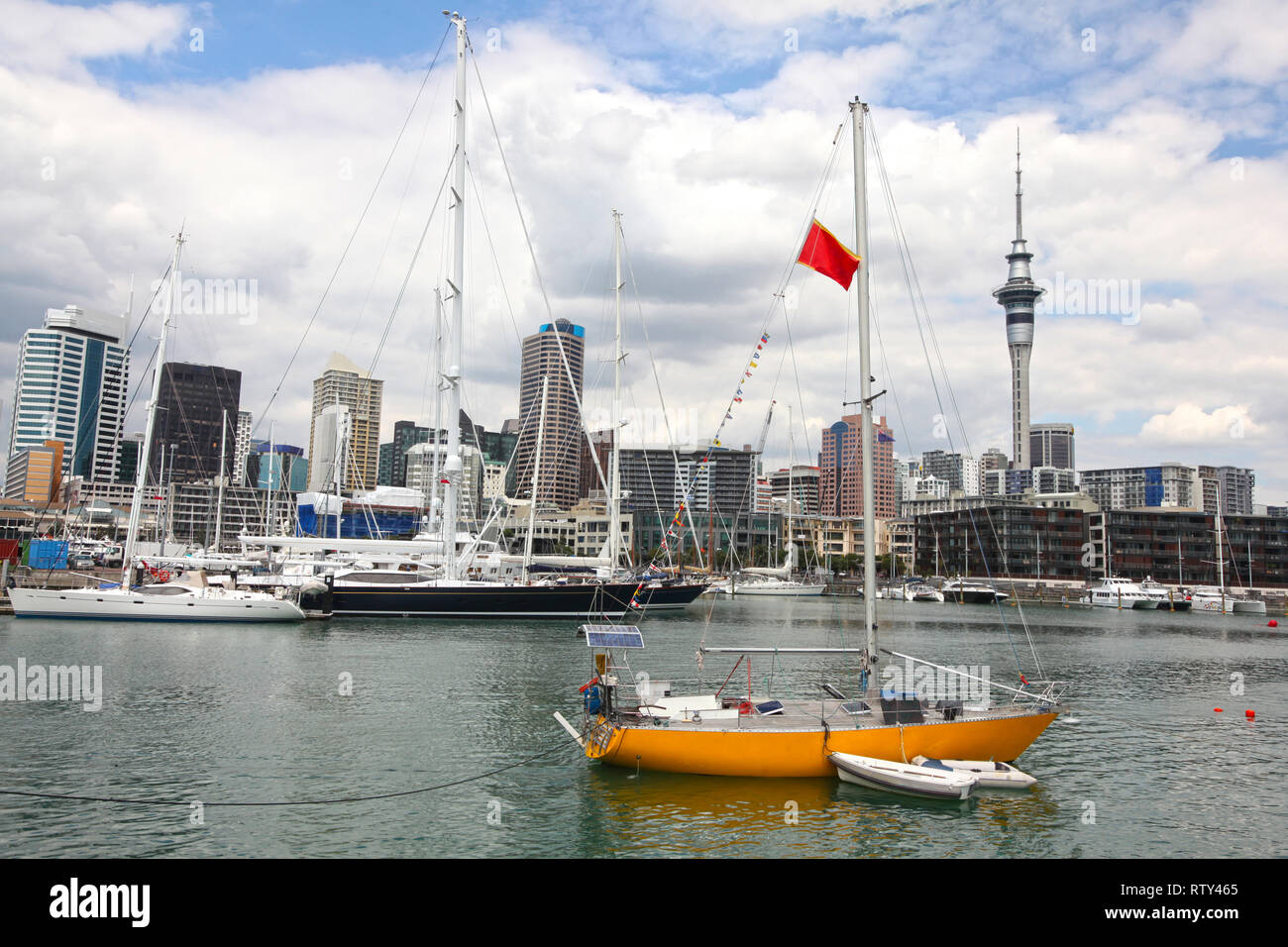 City view of Auckland, with high rise skyscrappers in the background and a yellow sailing boat in the foreground, North Island, New Zealand. - Stock Image