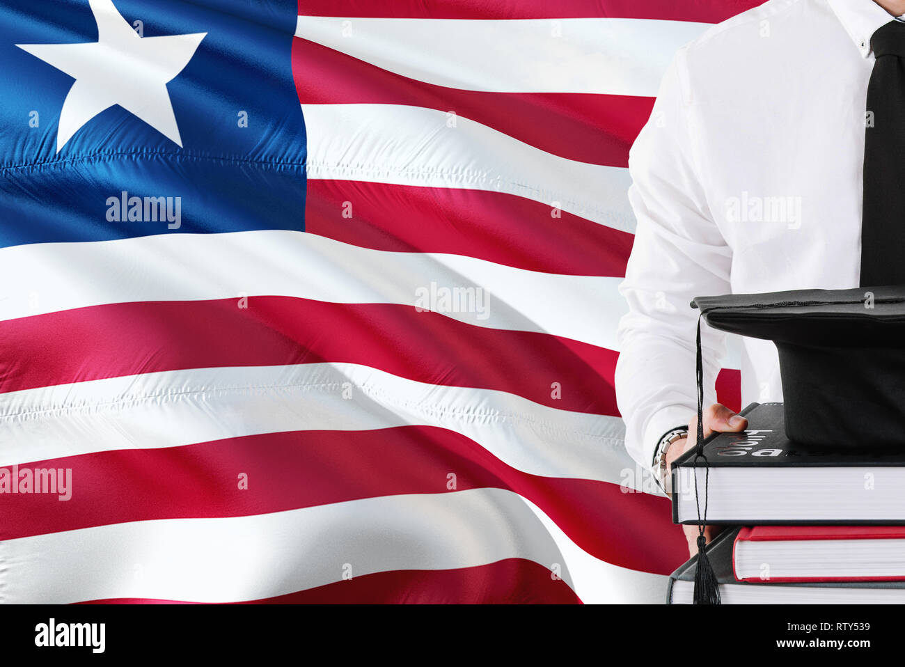 Successful Liberian student education concept. Holding books and graduation cap over Liberia flag background. - Stock Image
