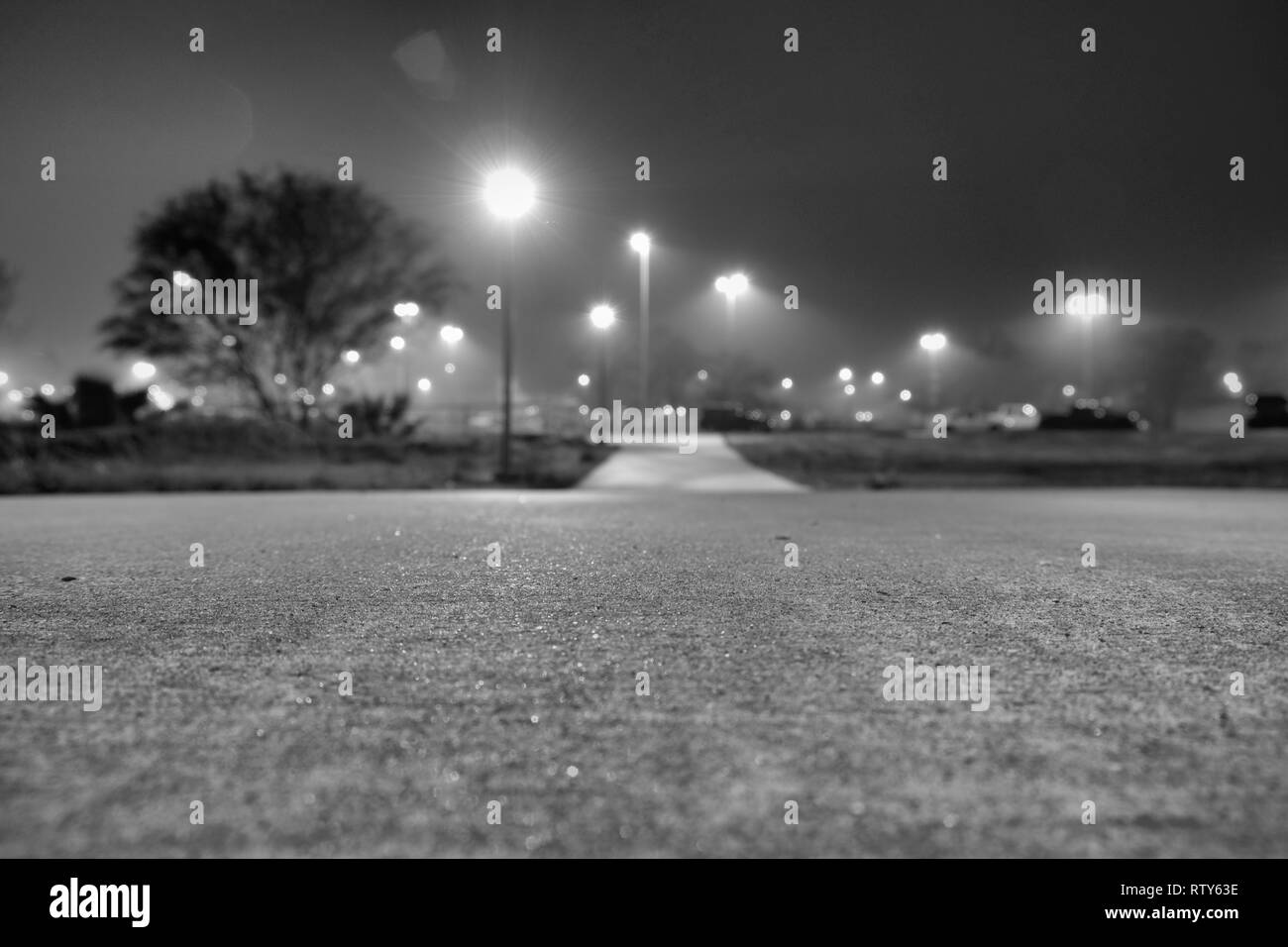Low perspective view of a cement walkway with streetlights causing lens flare; focus on immediate space in front of lens; College Station, Texas, USA. - Stock Image
