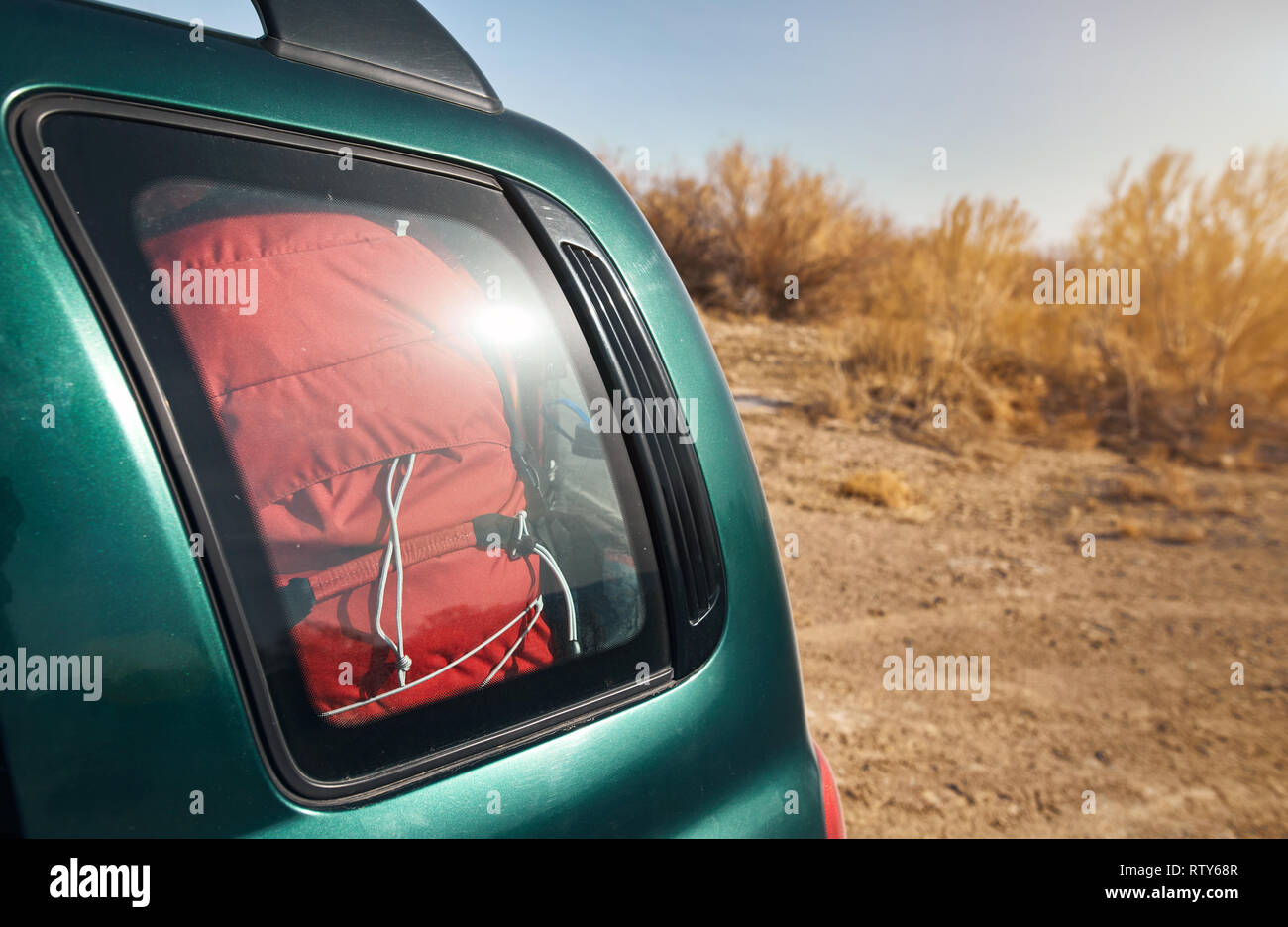Red backpack in car trunk at the nature background - Stock Image