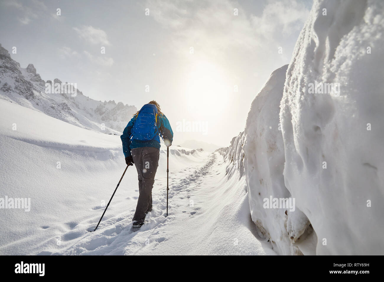 Tourist with blue backpack walking on the snow road in the mountains at snowfall - Stock Image