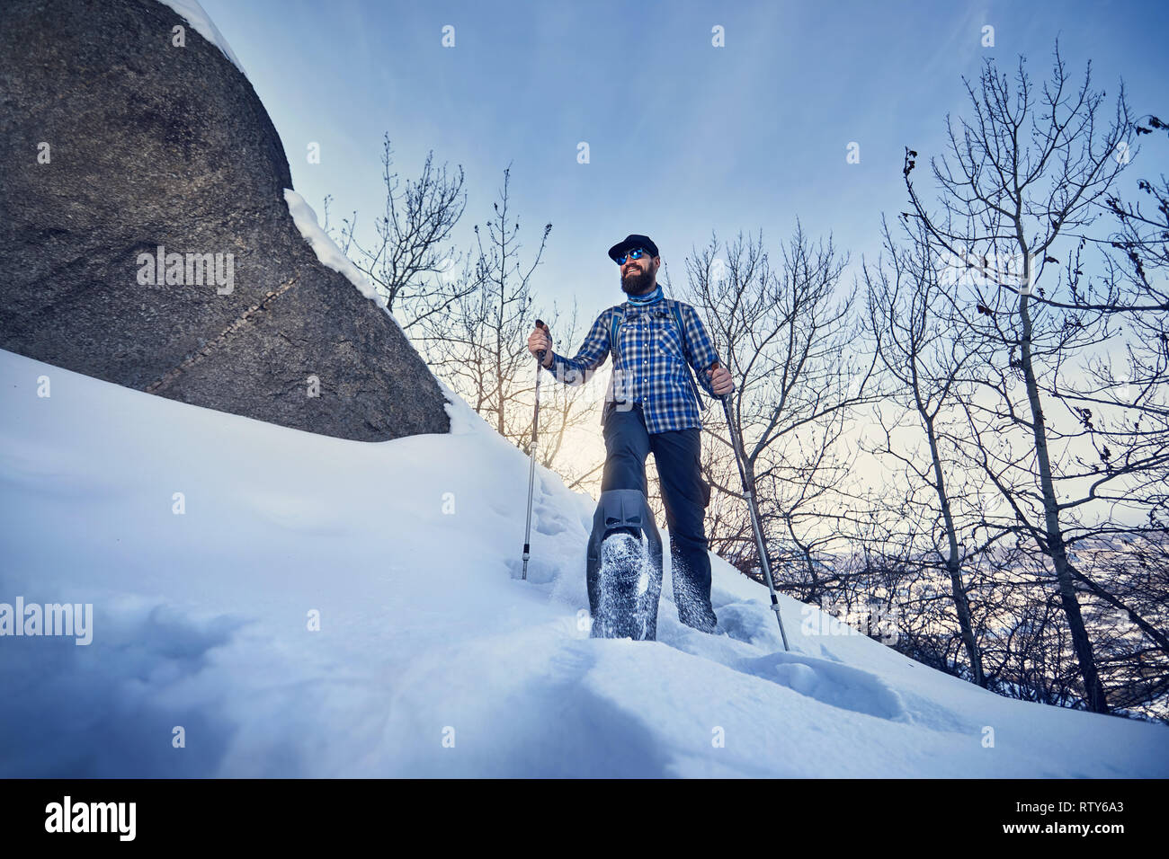 Happy Hiker with beard in snowshoes at winter forest at blue sky background - Stock Image